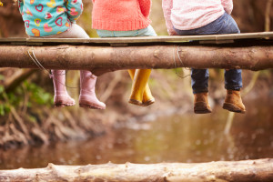 Close Up Of Children's Feet Dangling From Wooden Bridge